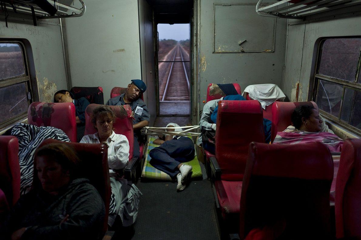 Um homem dorme no chão de um trem viajando de Havana para Santiago de Cuba.
