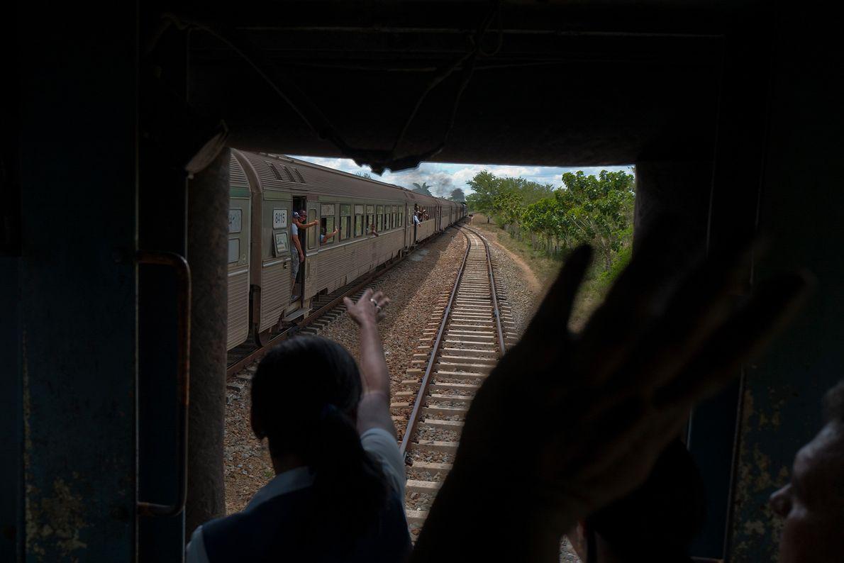 Passageiros acenam uns para os outros através das janelas do trem.