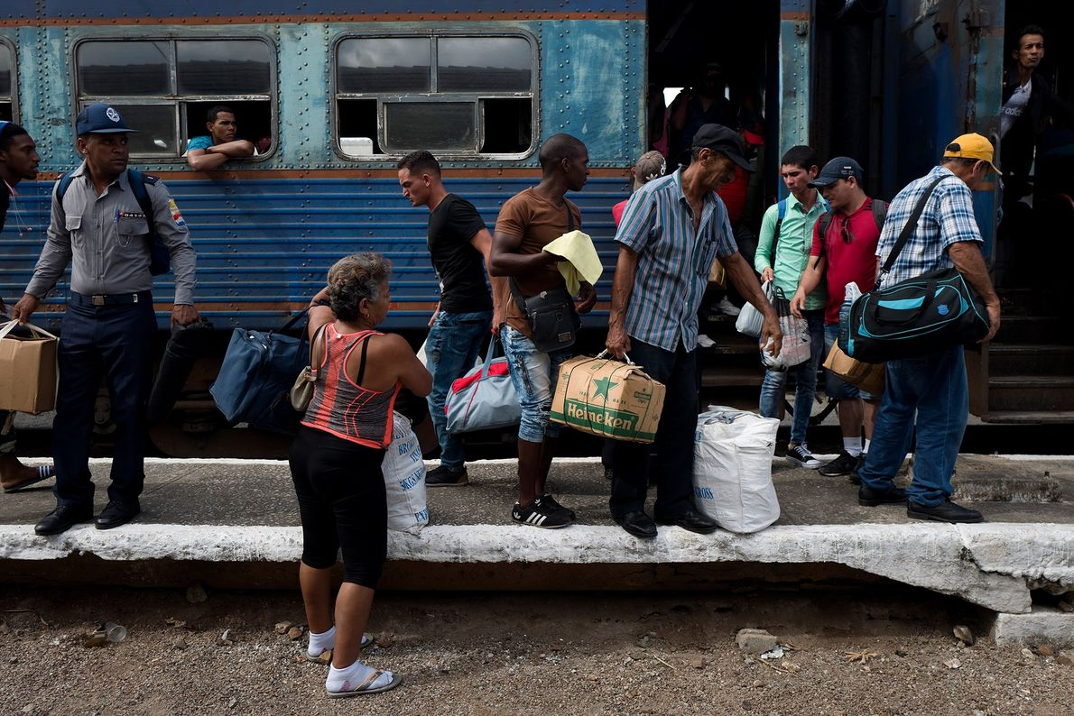 Passageiros carregam suas malas e pacotes ao descer do trem na estação de Camaguey.