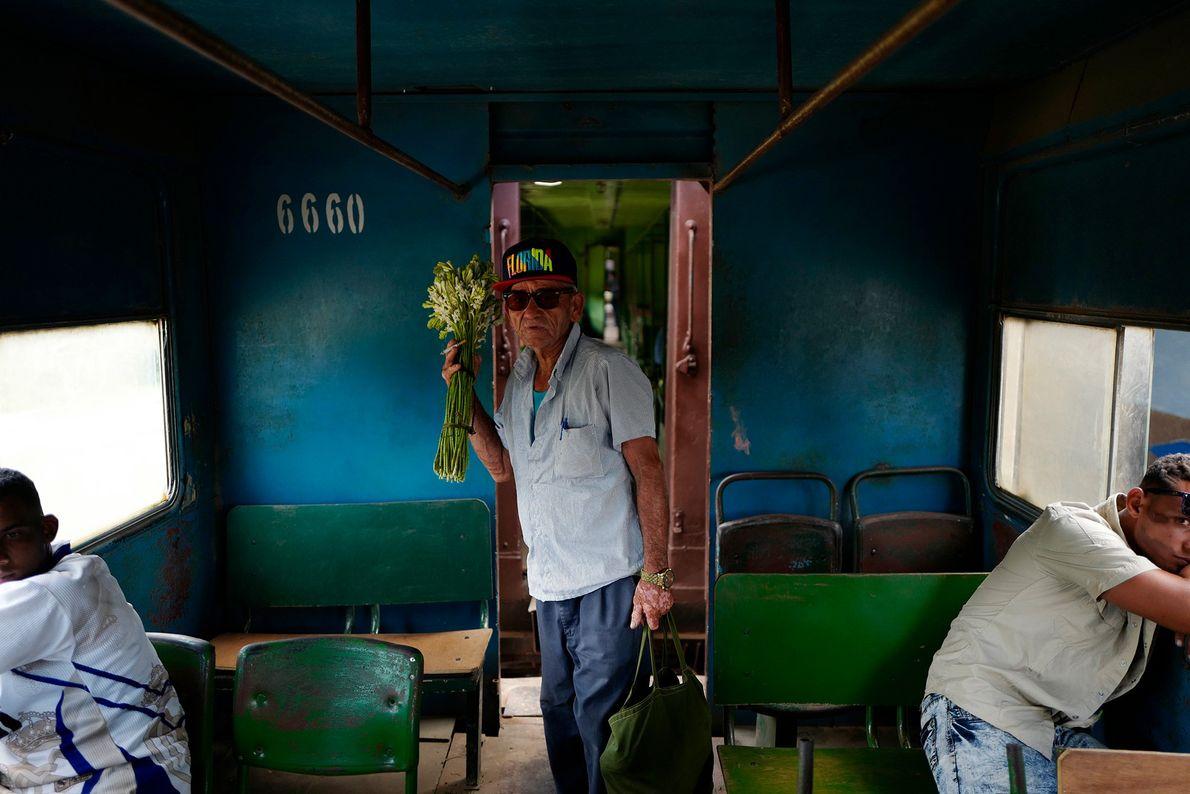 Um homem carrega um buquê de flores no trem de Santiago de Cuba para Bayamo.