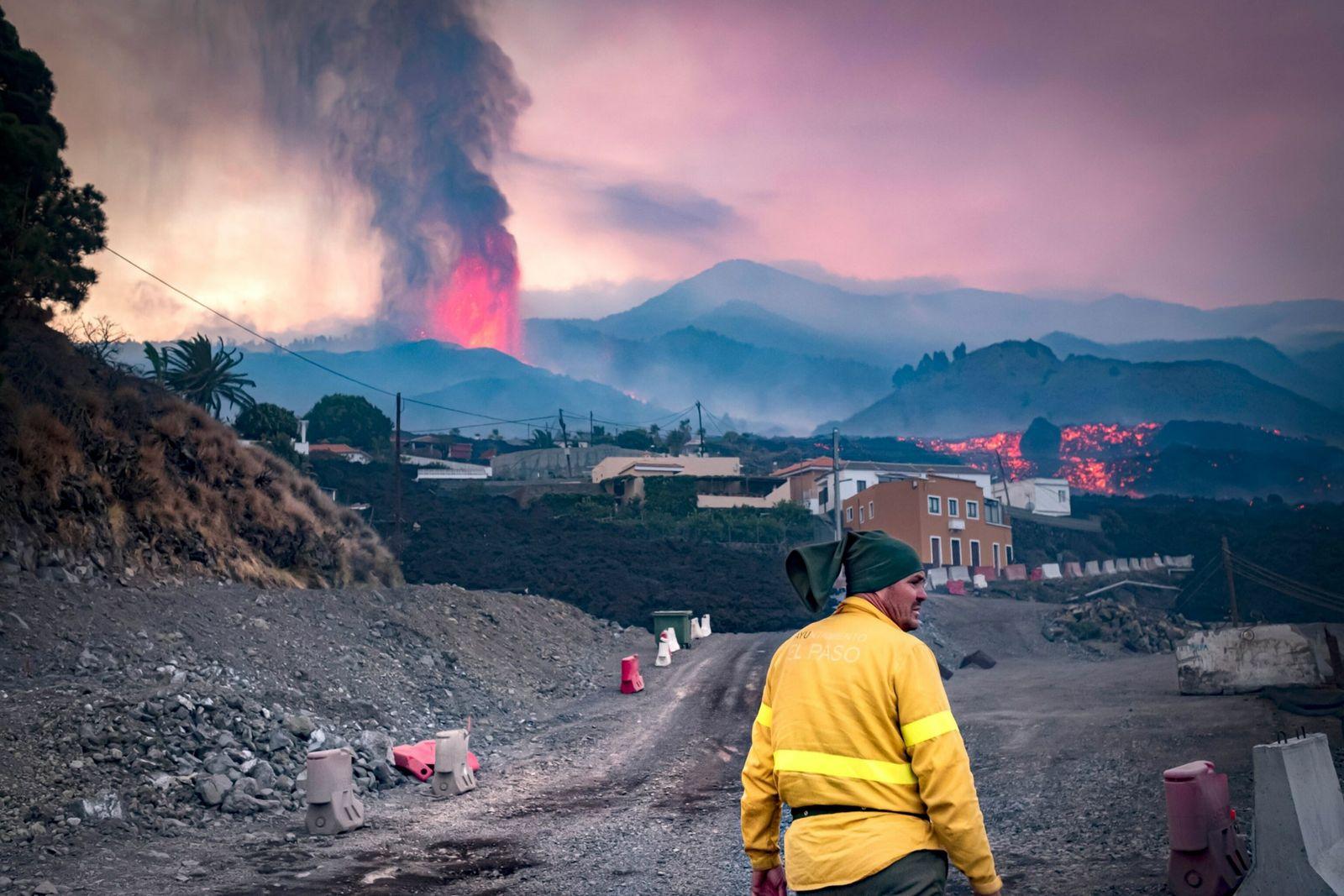 Foto de bombeiro em primeiro plano com vulcão em erupção ao fundo