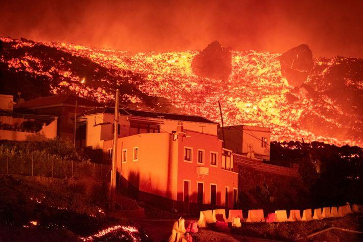 foto de casa com lava de vulcão ao fundo