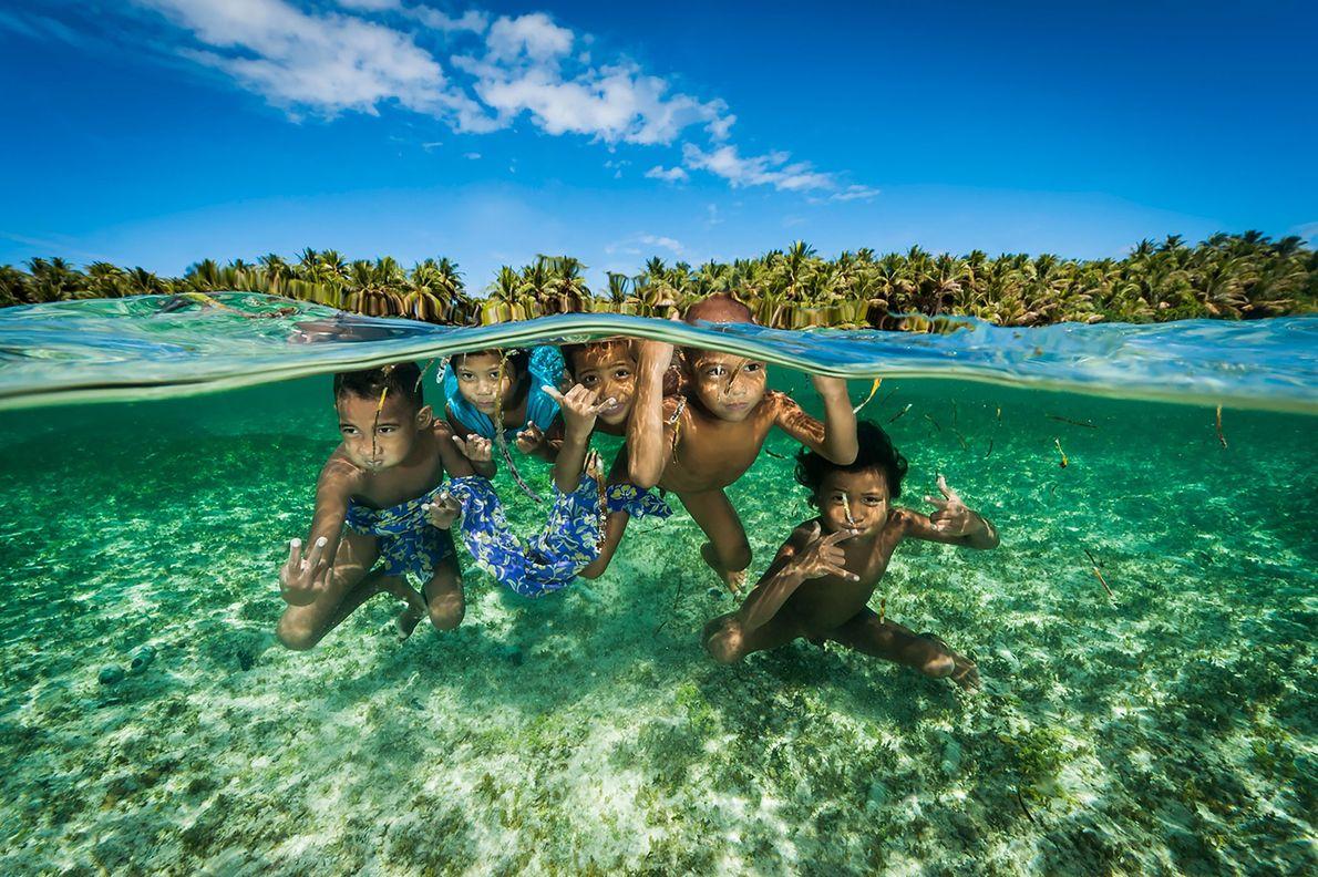 Descendentes dos lendários navegadores da Ilha Satawal brincam nas águas quentes das Ilhas Carolina nos Estados ...