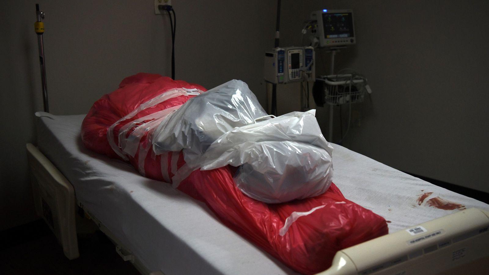 Um homem que faleceu em decorrência do coronavírus envolto em um saco mortuário na unidade de ...
