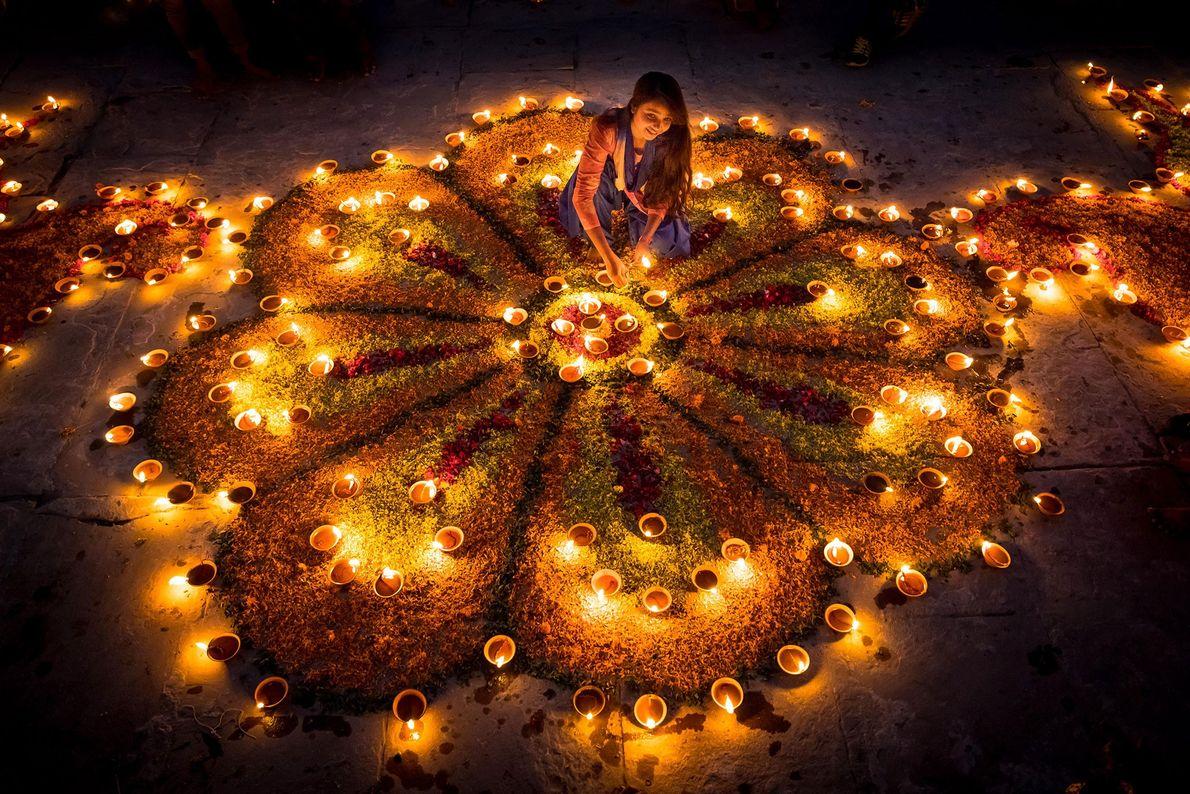 Durante o Dev Diwali em Varanasi, esta jovem cria padrões rangoli no chão com flores e ...