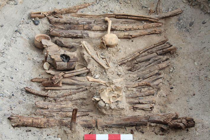 Um recipiente de madeira para queima pode ser visto à esquerda desta sepultura escavada no cemitério ...