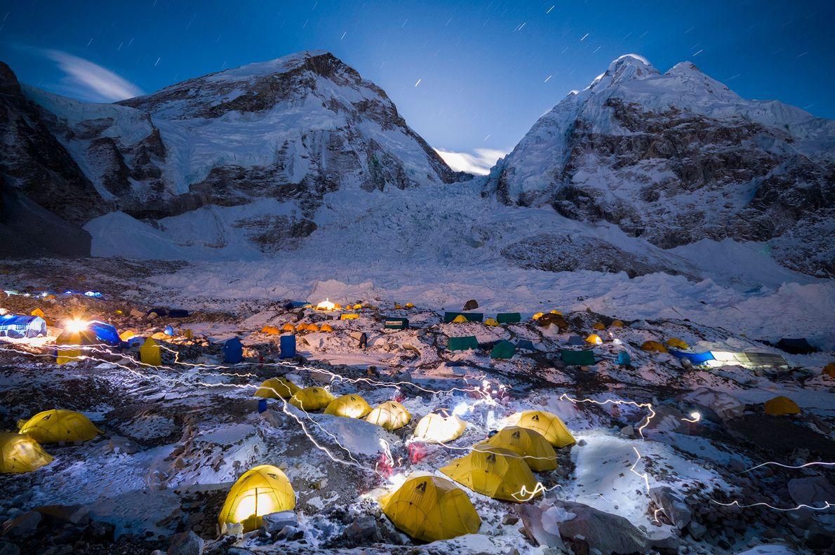 À noite, lanternas de cabeça dão destaque ao Acampamento Base Khumbu no Monte Evereste, Nepal. Circundado ...