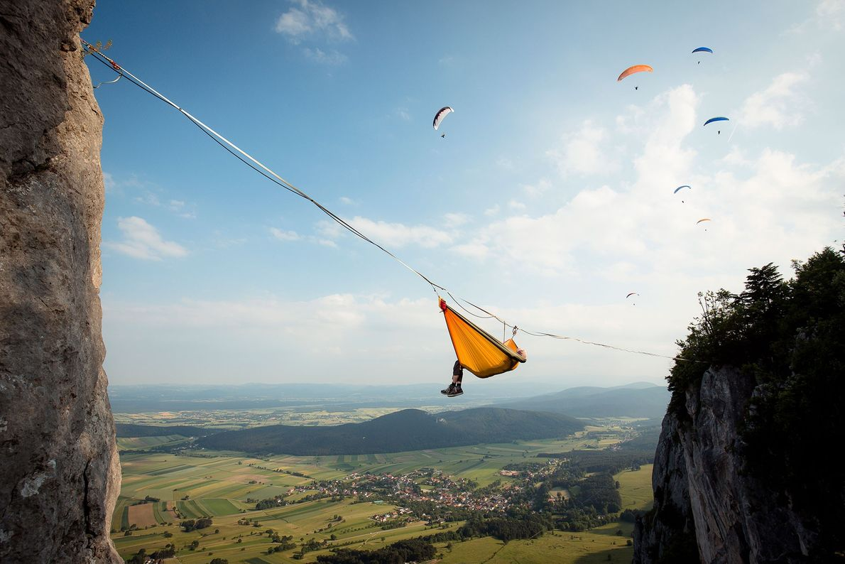 O atleta Thomas Spoettl descansa pendurado em seu highline nos Alpes australianos, enquanto pilotos de parapente ...