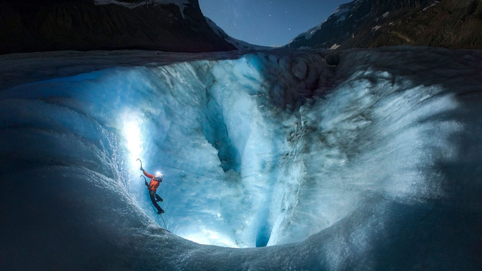 Sob o céu noturno, um alpinista de gelo avança pela Geleira Athabasca, que derrete em ritmo ...