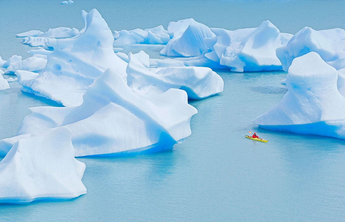 Um caiaquista navega em meio a incríveis icebergs no Lago Gray, Parque Nacional Torres del Paine, ...