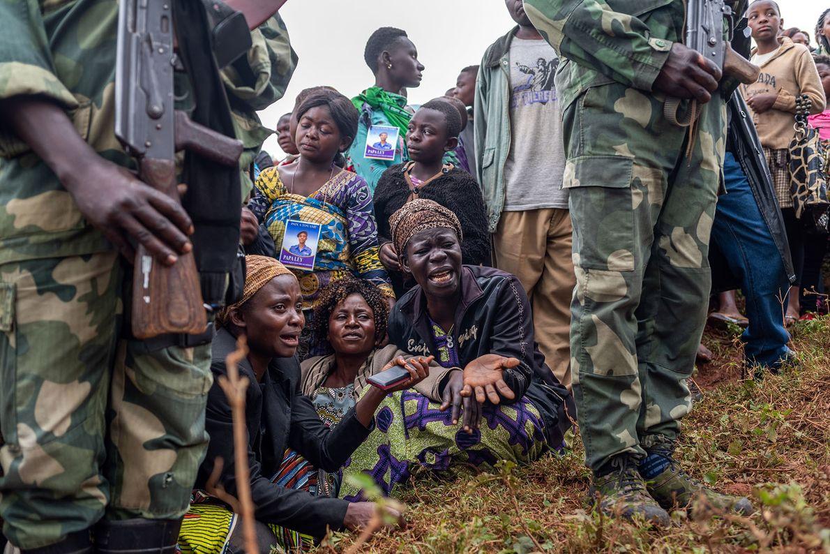 Amigos e familiares do policial Tabu Amuli Emmanuel em luto durante o enterro no cemitério Kitatumba, ...