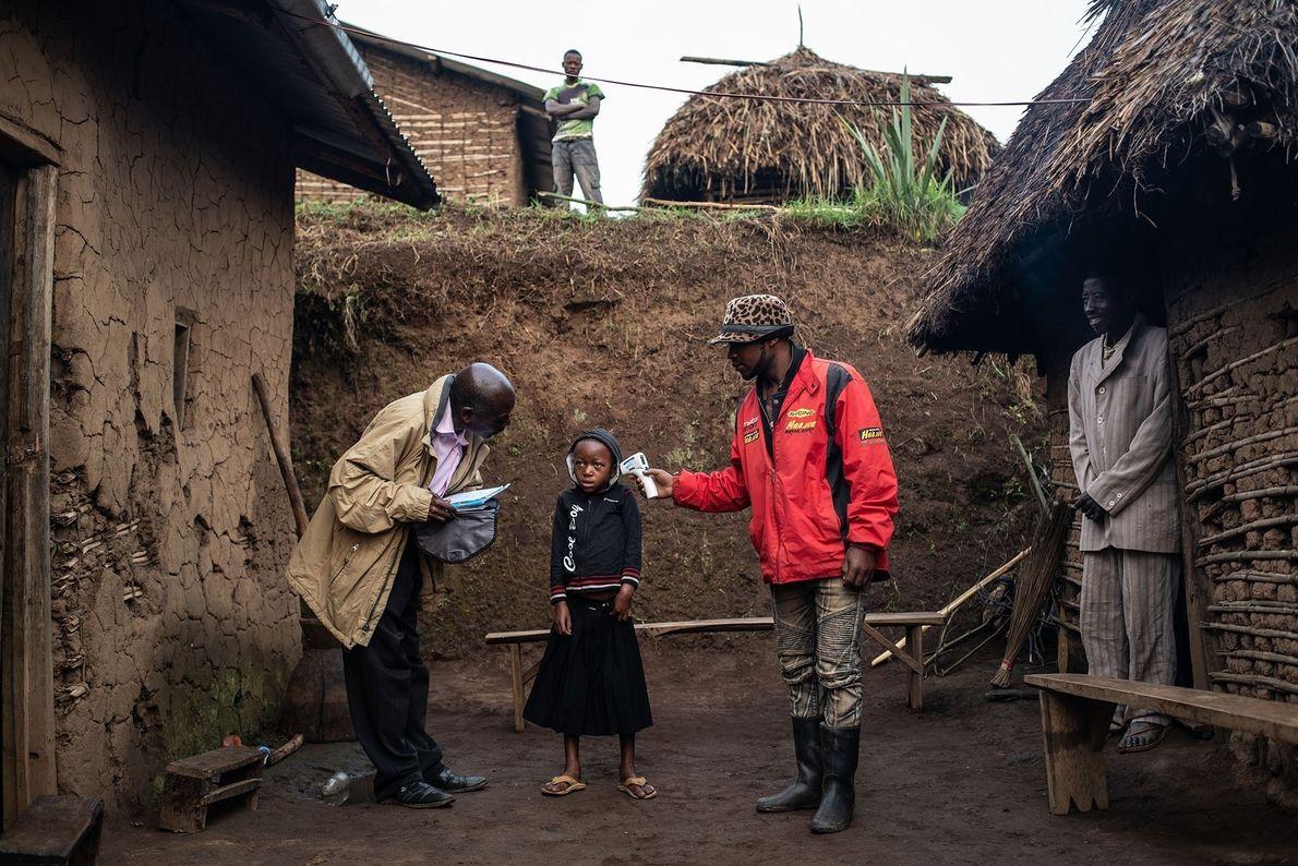 Uma equipe da Organização Mundial da Saúde verifica a temperatura de Confirme Masika Mughanyira, com sete ...