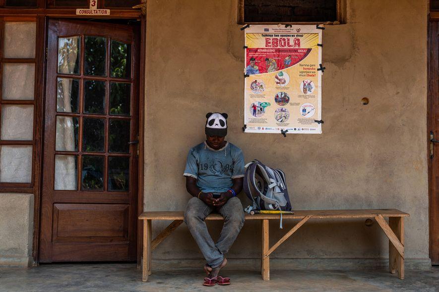 Um jovem aguarda na parte externa de uma clínica privada em Beni em 27 de fevereiro ...