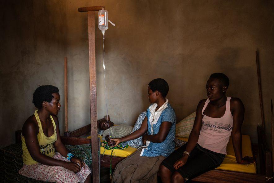 Três irmãs sentadas com o irmão de 14 anos, Kakule Kavendivwa, um caso de suspeita de ...