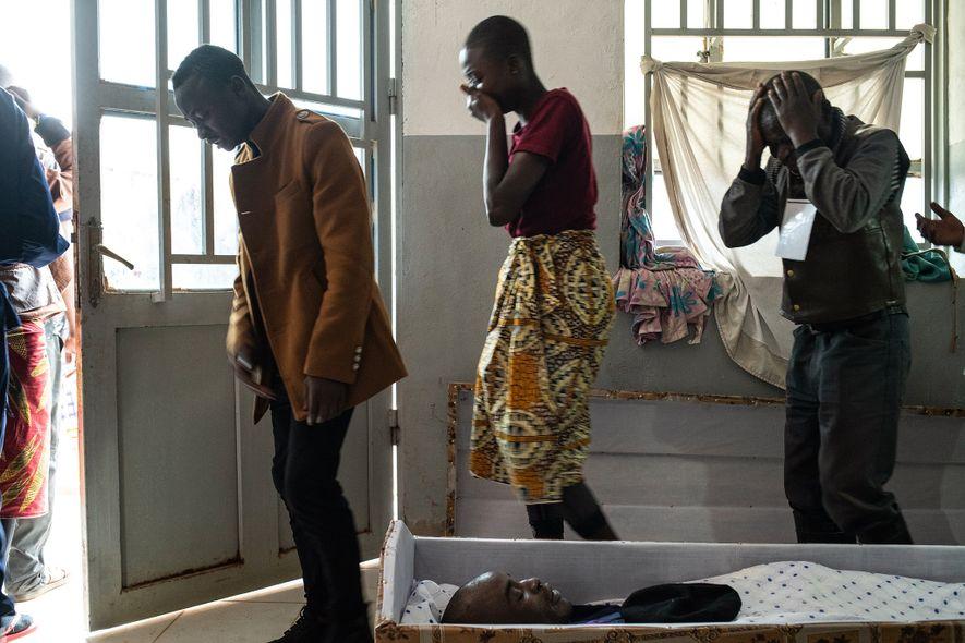 Família e amigos observam o corpo do policial Tabu Amuli Emmanuel no necrotério do Hospital de ...