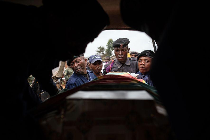 Policiais colocam o caixão de Tabu Amuli Emmanuel, 50 anos, em um veículo que transportará o ...