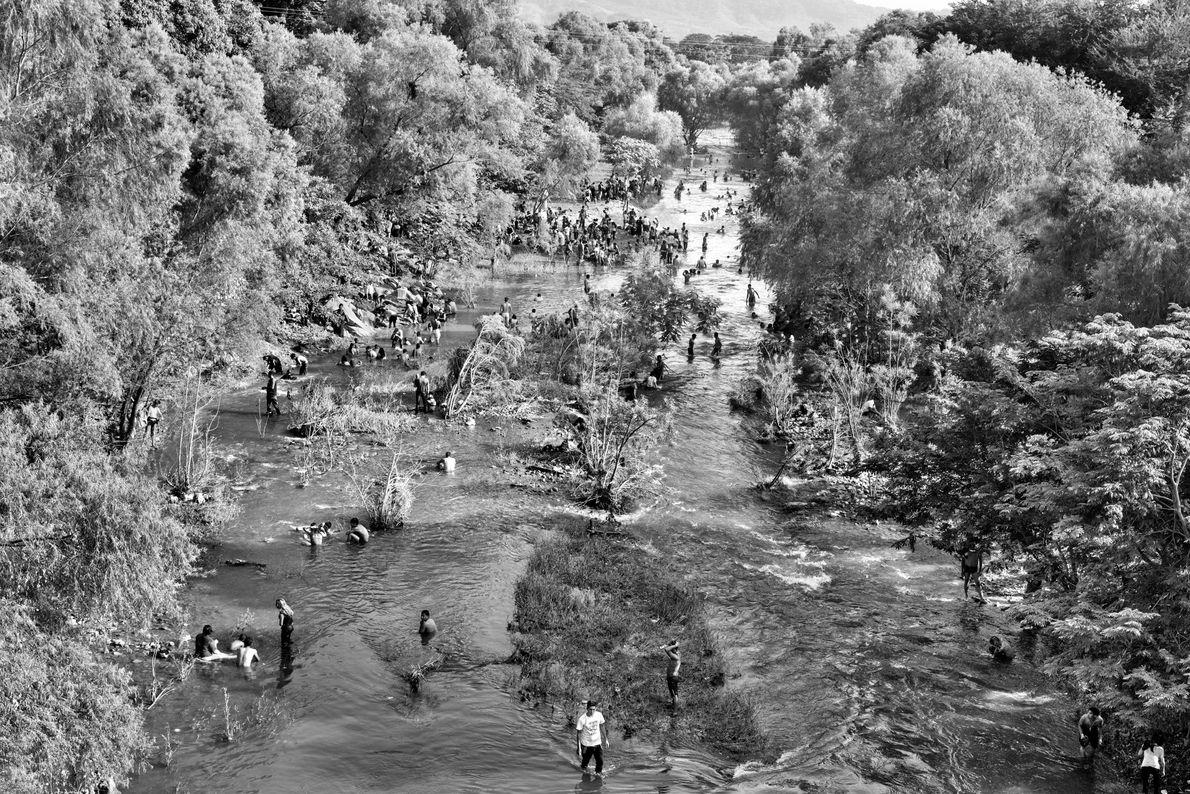 Centenas de imigrantes da América Central se refrescam, tomam banho e limpam as roupas no rio ...