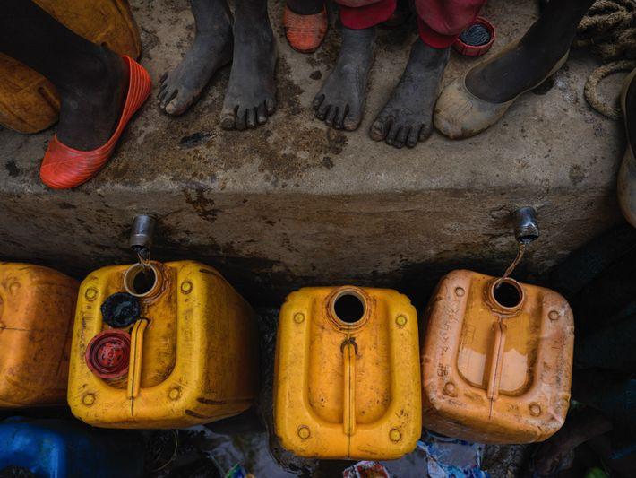 Detalhe de pés de crianças que se espremem na fila para coletar água em uma bica ...