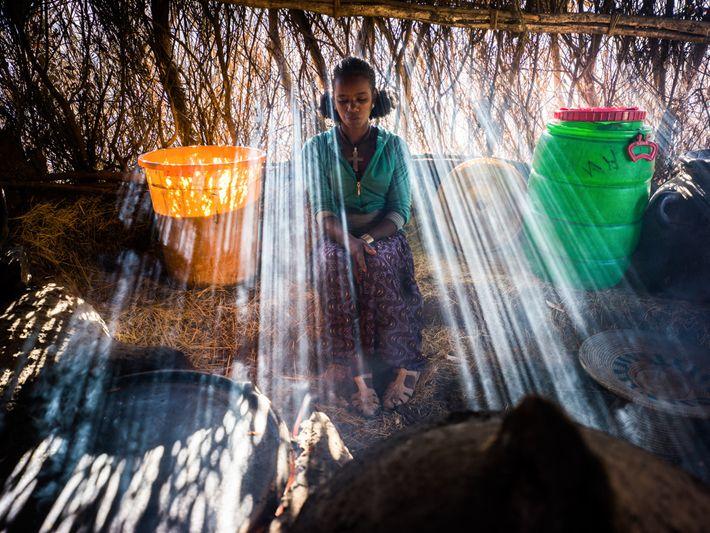 Mulher prepara o fogo e usa água que acabara de pegar no rio para poder preparar ...