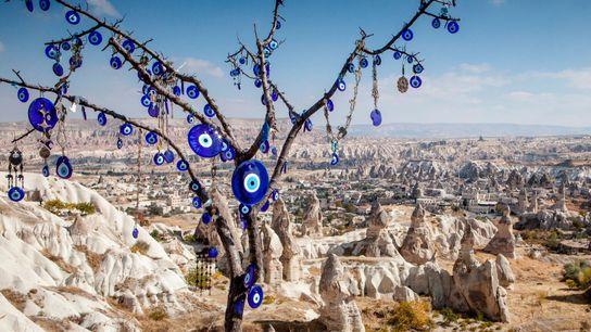 Nos arredores da Capadócia, na Turquia, talismãs azuis de vidro contra o mau-olhado enfeitam uma árvore. ...