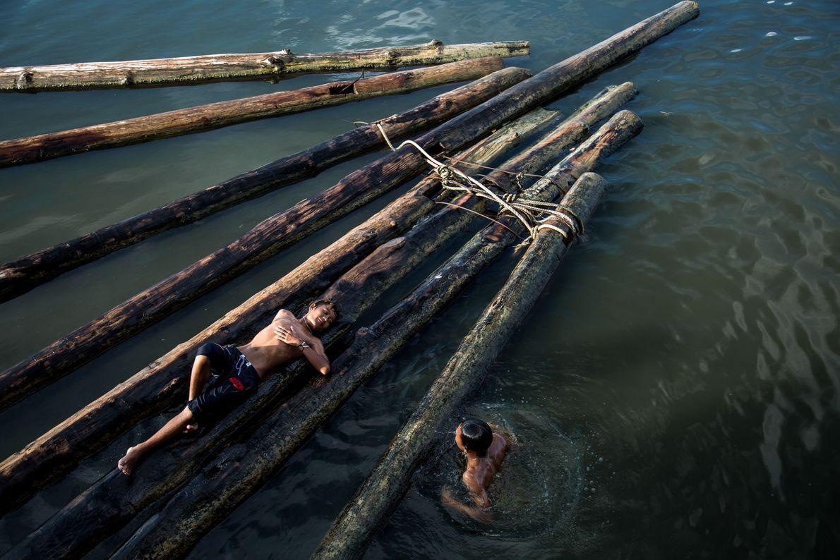 Crianças em cima de troncos flutuantes
