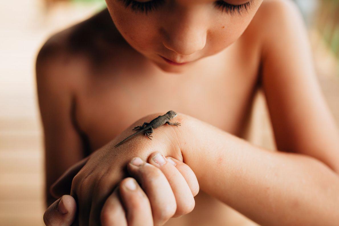 Menino com lagarto na mão