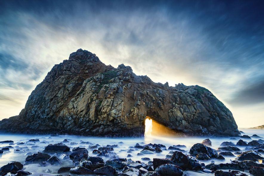 Arco esculpido em pedra com luz solar passando por ele no meio do mar
