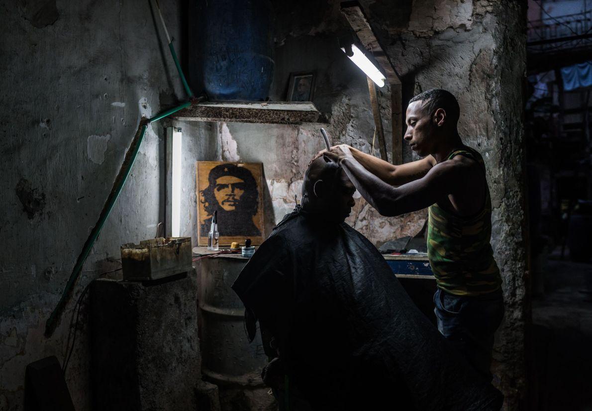 Barbeiro corta cabelo de homem em Cuba. Ao fundo, foto de Che Guevara