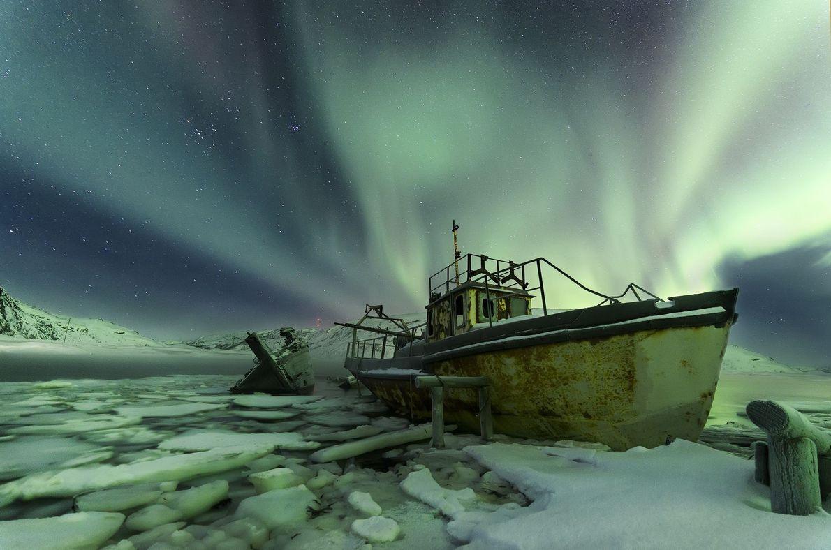 Barcos com aurora boreal atrás