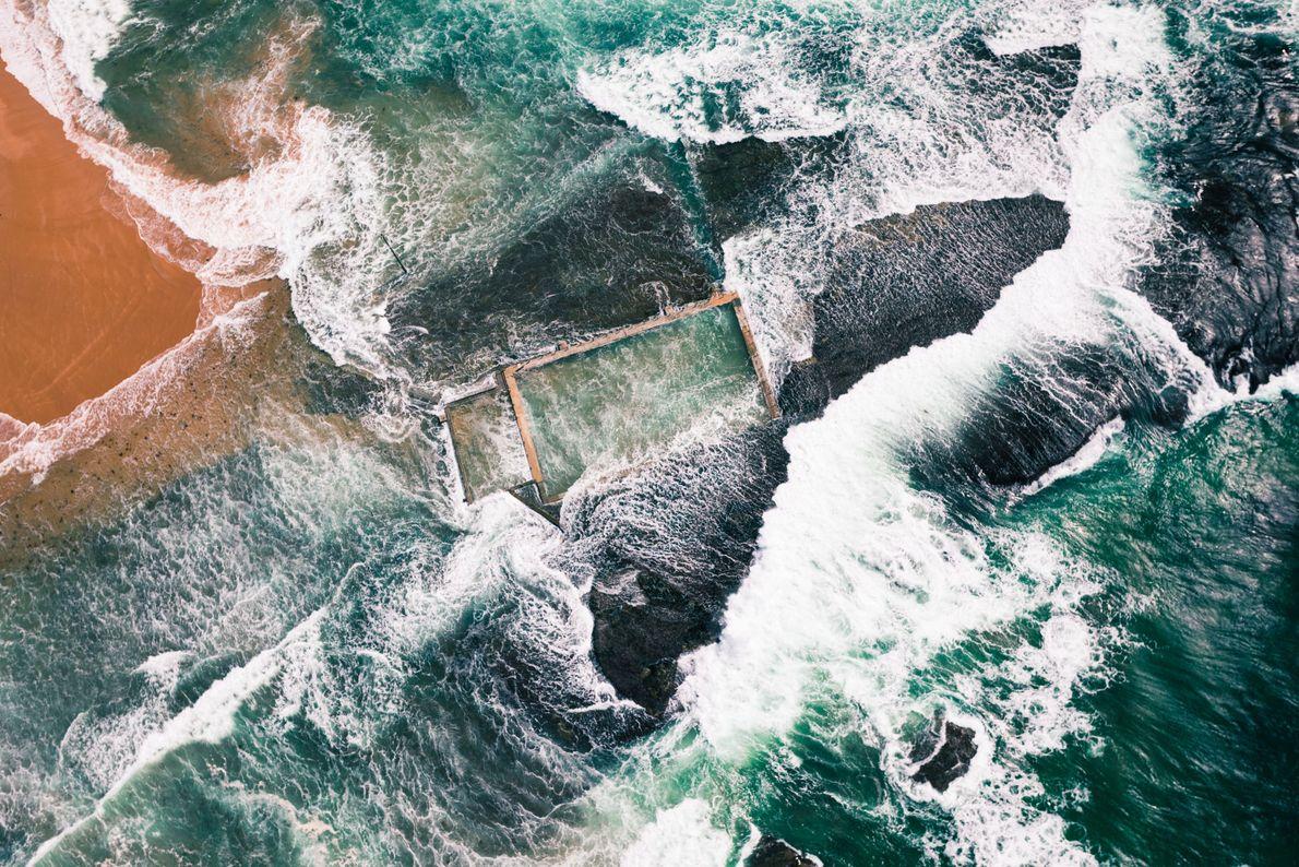 Ondas quebram em uma piscina construída no mar