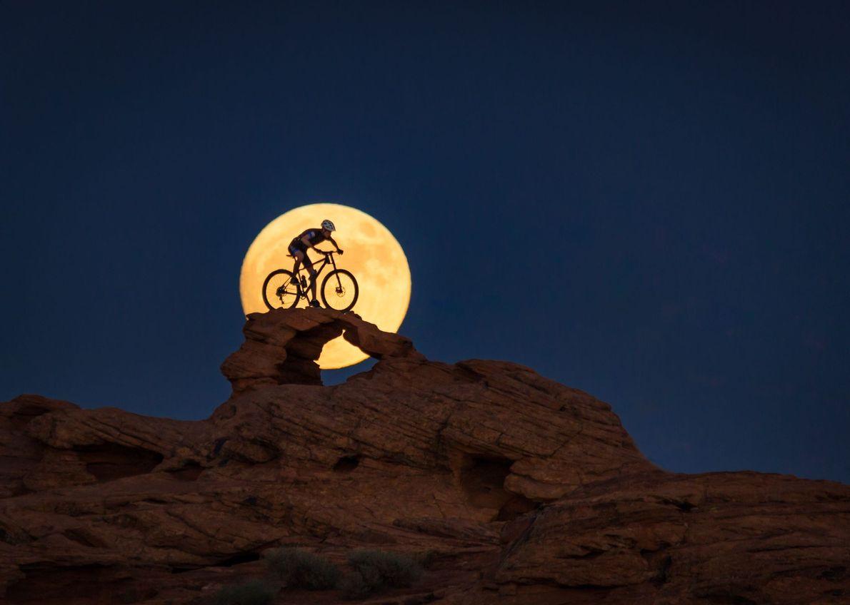 Homem andando em bicicleta no deserto e lua por trás
