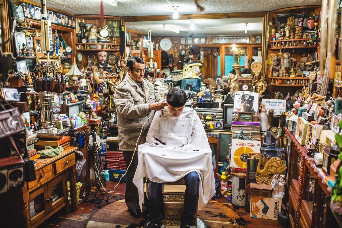 Barbeiro cortando cabelo em barbearia cheia de coisas