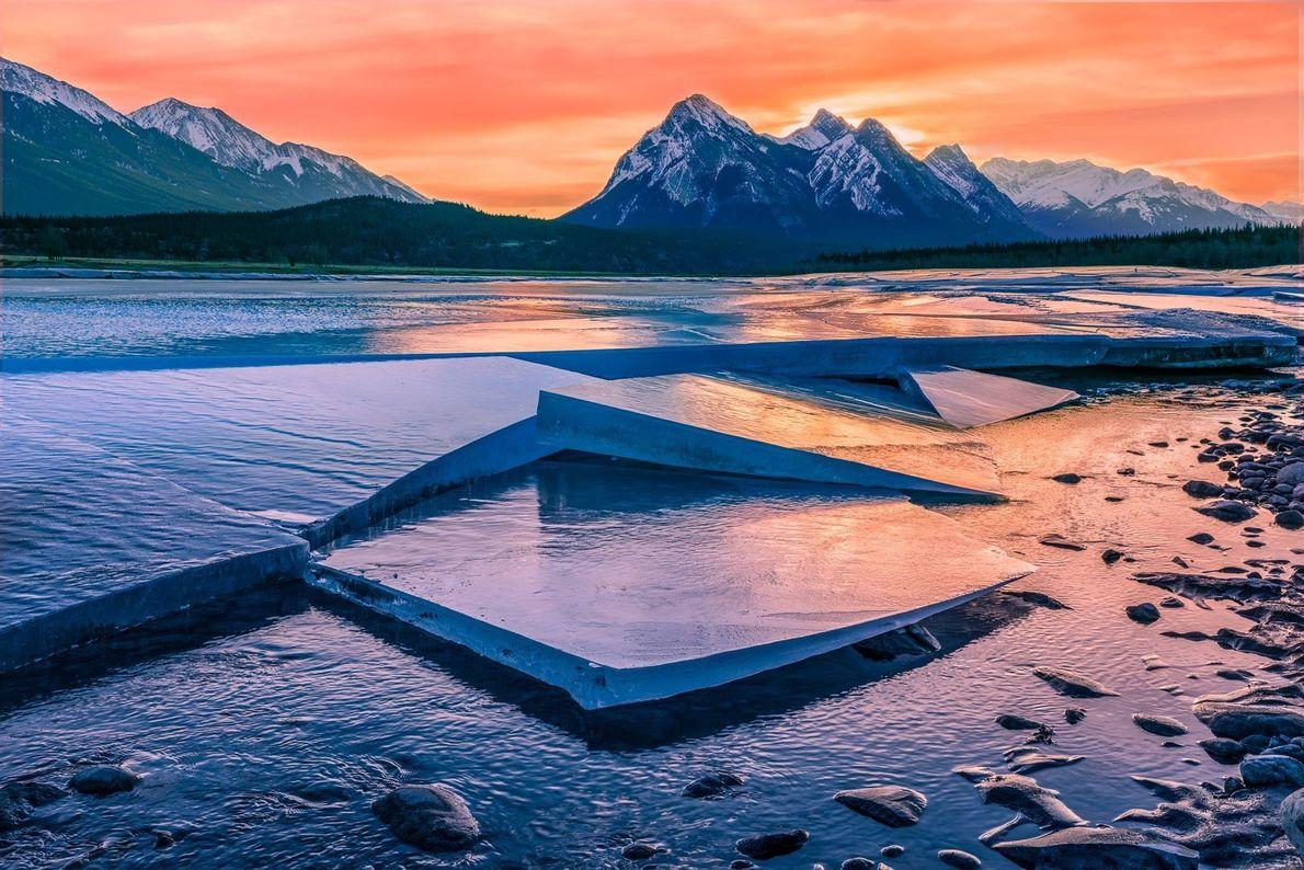 Sol nascendo por trás de montanhas em Abraham Lake, no Canadá