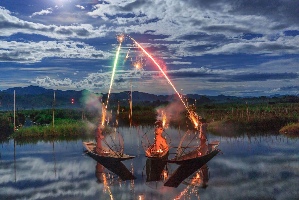 Pescadores em barco soltando fogos de artifício em rio