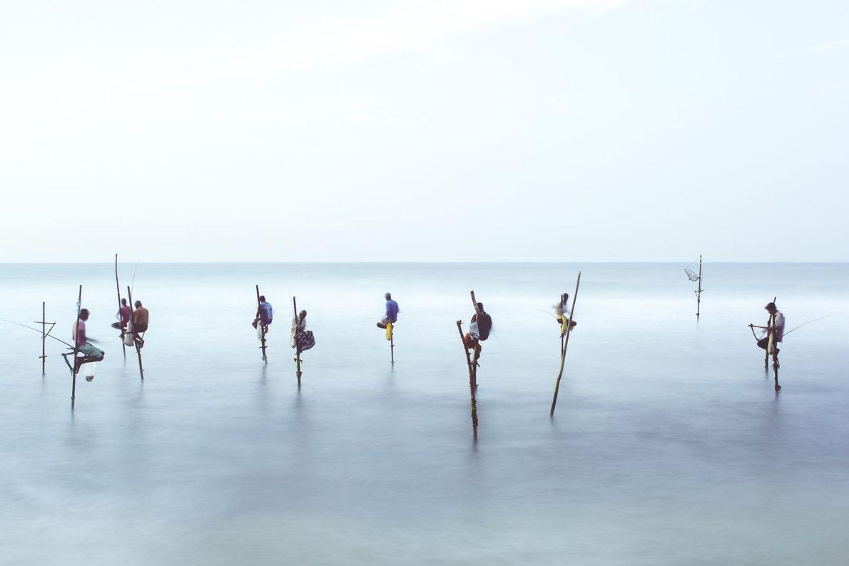 Pescadores em cima de pernas de pau andam sobre mar