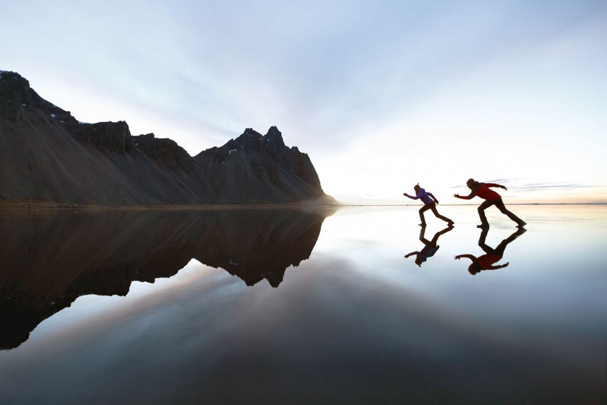 Duas pessoas andando sobre um lago e uma montanha no horizonte