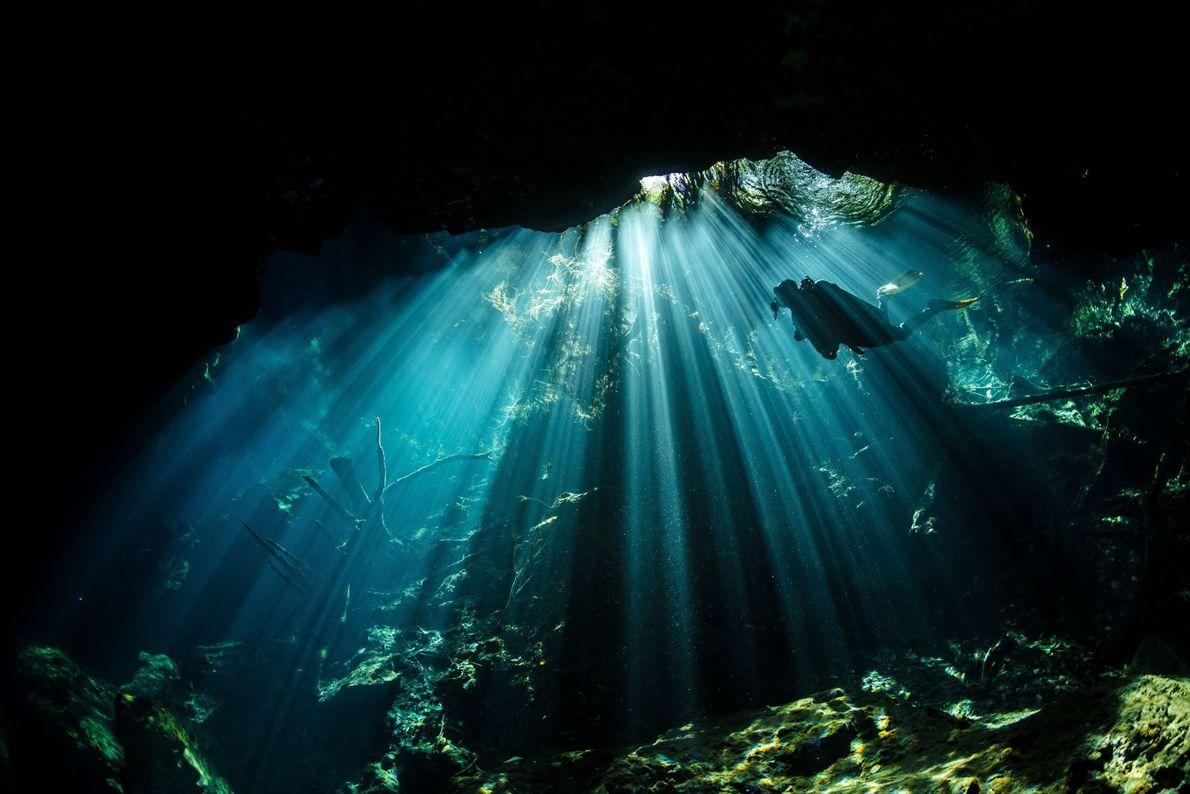 Mergulhador nada em caverna embaixo de água