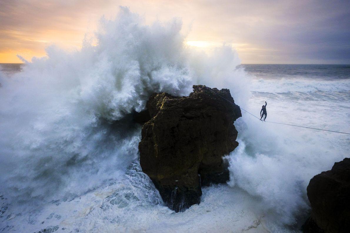 Homem andando em slackline com ondas e mar ao redor