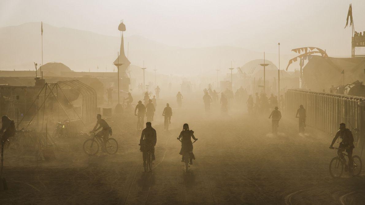 Pessoas andam de bicicleta em uma cidade cheia de poeira
