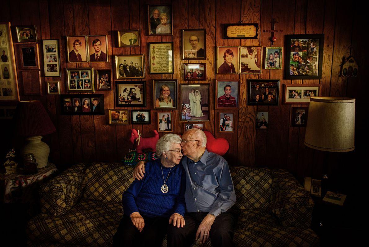 Casal de idosos em frente a fotografias