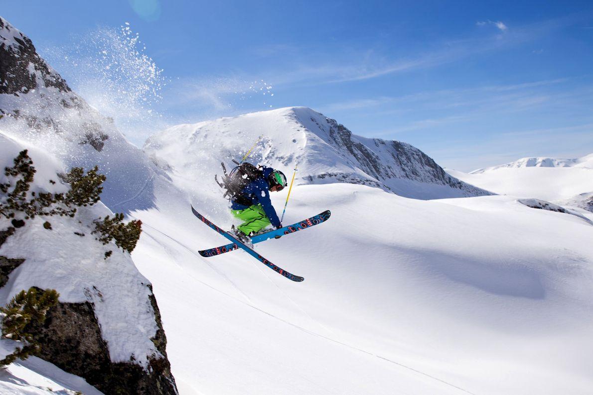Esquiador salta em montanha coberta de neve