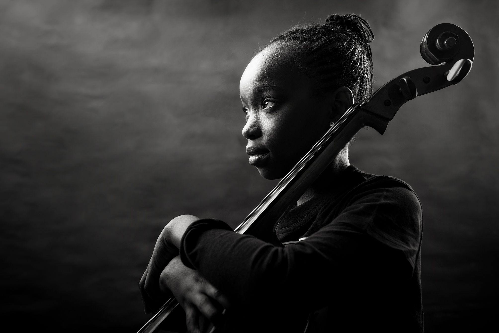Jovem violoncelista segura o instrumento