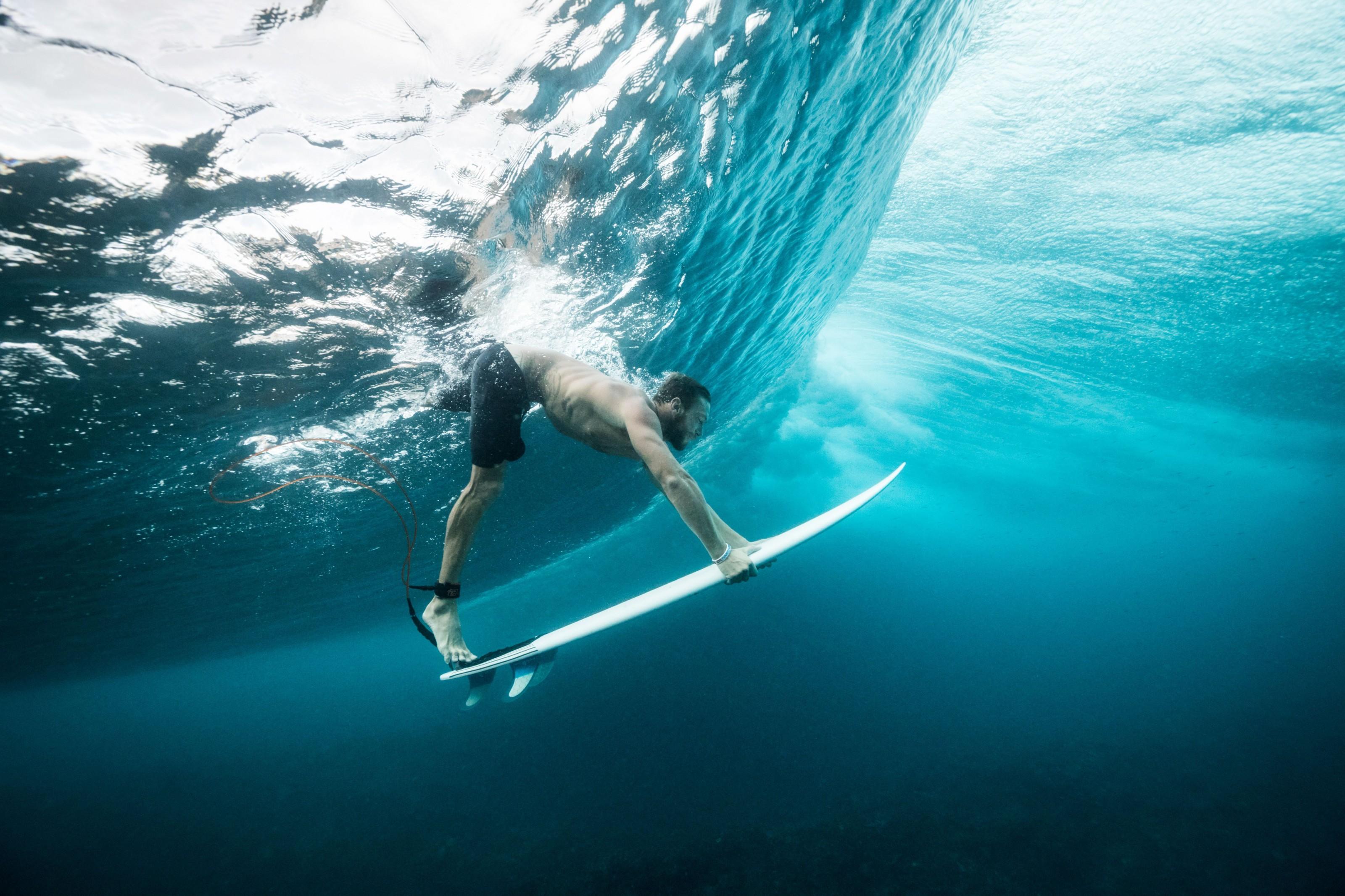foto de surfista abaixo de uma onda