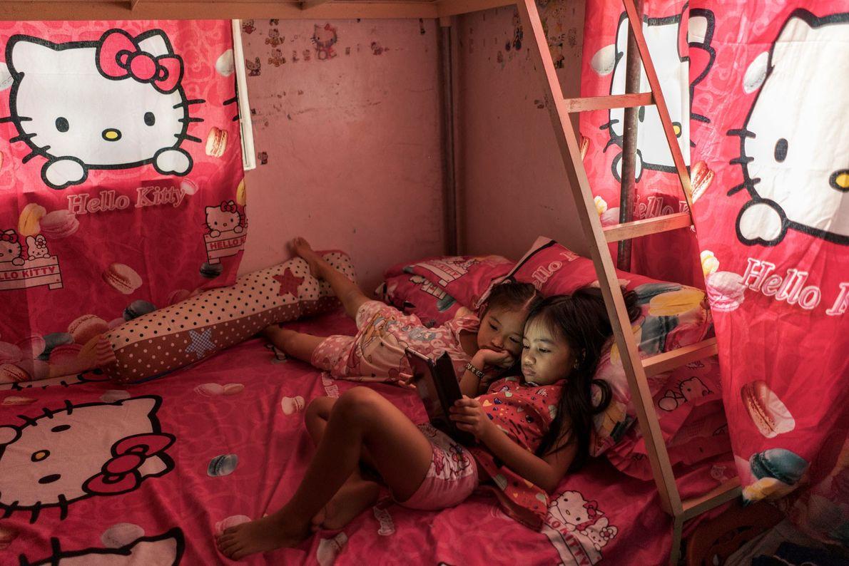 Althea Tolidanes, 8, assiste a vídeos em meio a lençóis, travesseiros e cortinas, presentes de seu ...