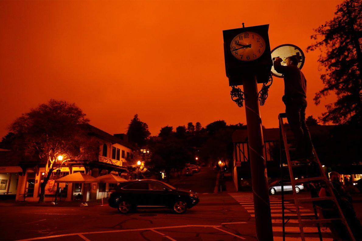 Com o céu brilhando através da fumaça de incêndio, Bejhan Razi, inspetor sênior de construções de ...
