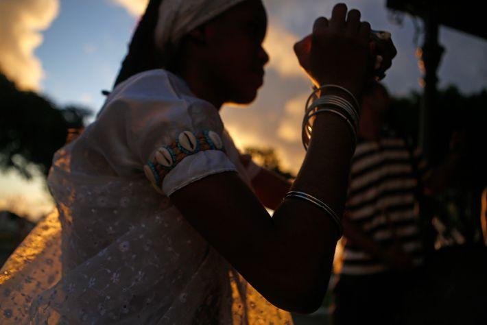 Uma praticante de candomblé dá um banho de pipoca em um transeunte, um ritual comum de ...