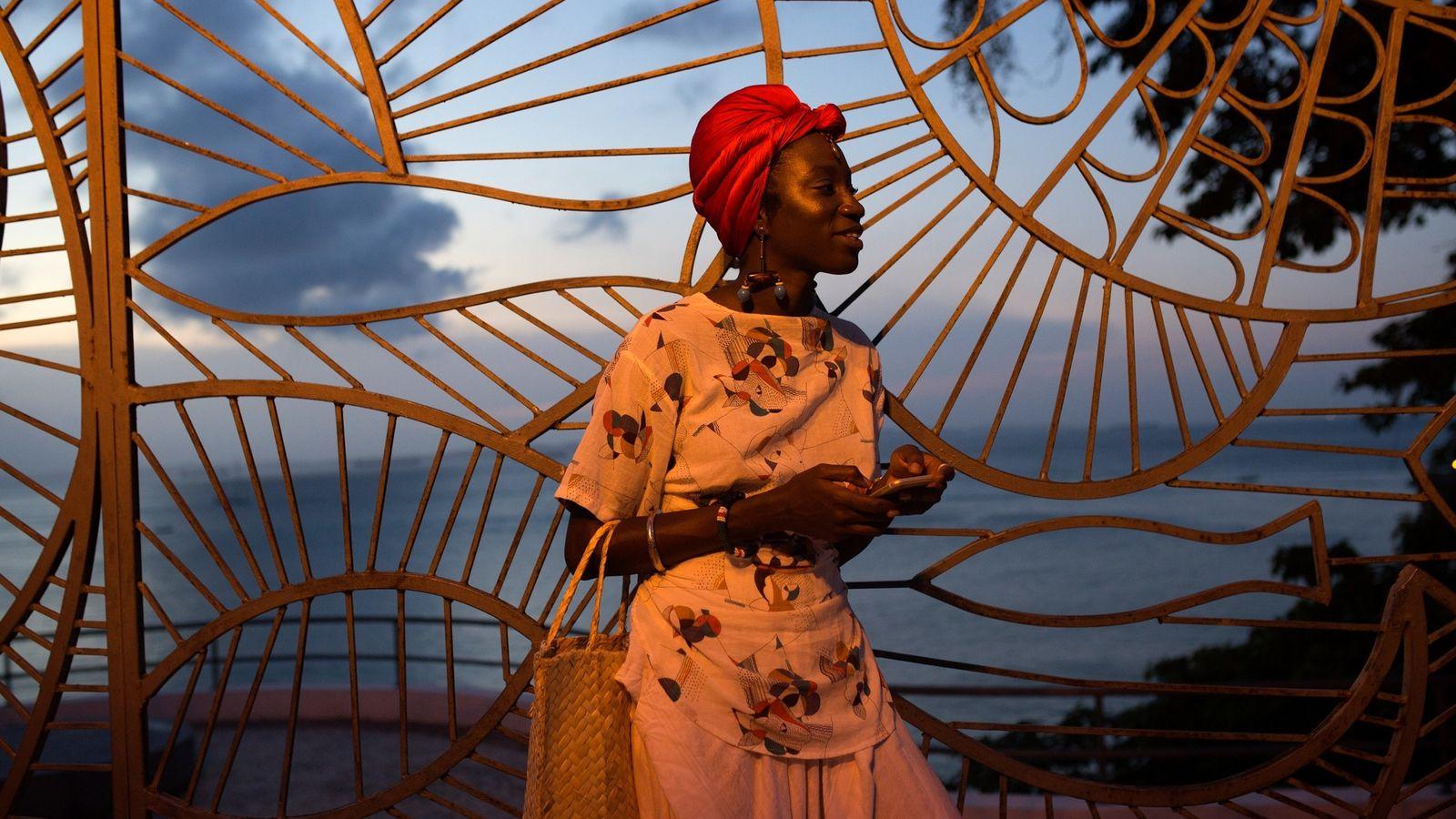 Luma Nascimento espera por um táxi em uma movimentada rua de Salvador. Luma faz parte do ...