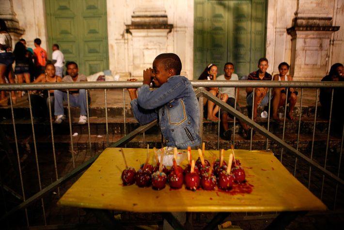 Um menino vende maçãs-do-amor durante as festas de São João, em frente à catedral de Salvador. ...