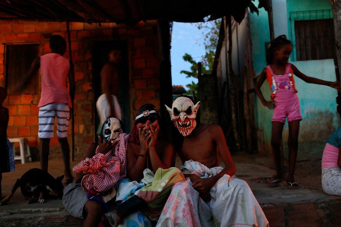 Meninos com máscaras e lençóis em frente de casa no vilarejo de Santiago do Iguape. As ...
