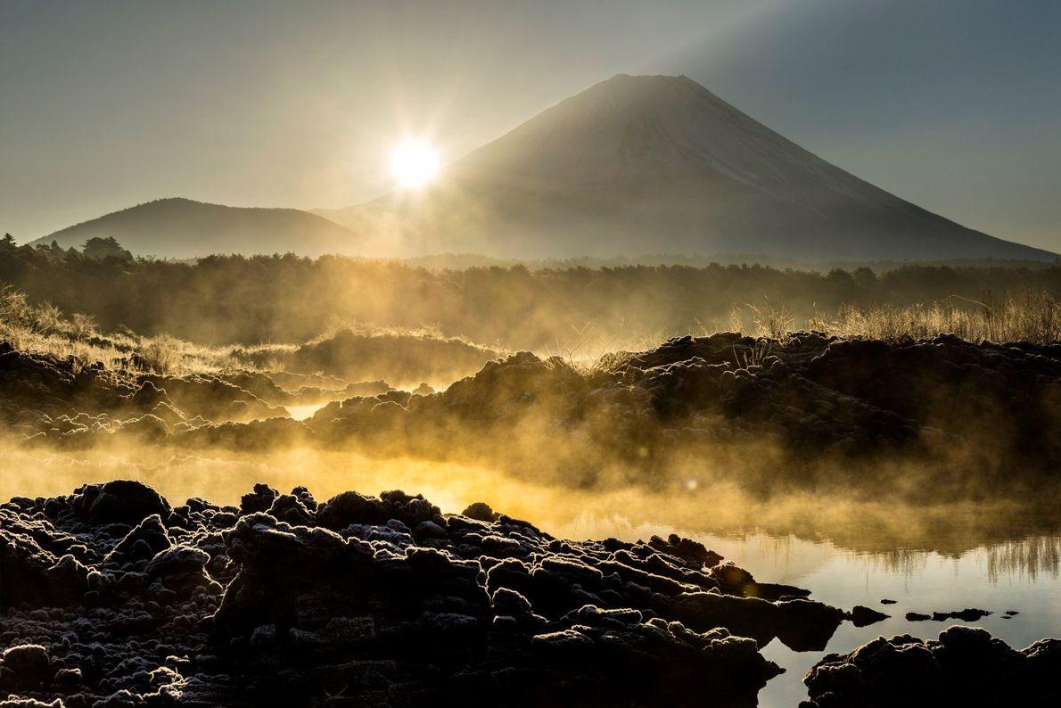 Em manhãs frias de inverno, a névoa sobe de um lago, iluminado pelo sol nascente.
